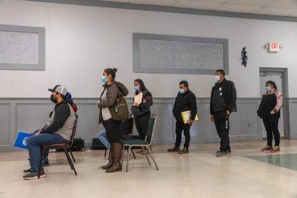 Salvadoreños con mascarillas esperan en una fila para recibir sus nuevos pasaportes en el consulado del país centroamericano en Chicago, Illinois (Foto: Reuters)