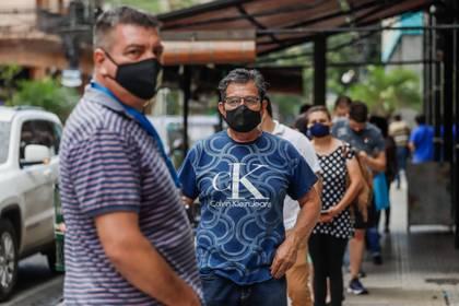 Varias personas hacen fila para entrar a un local comercial el pasado miércoles 20 de mayo del 2020 en Asunción (Paraguay). EFE/ Nathalia Aguilar
