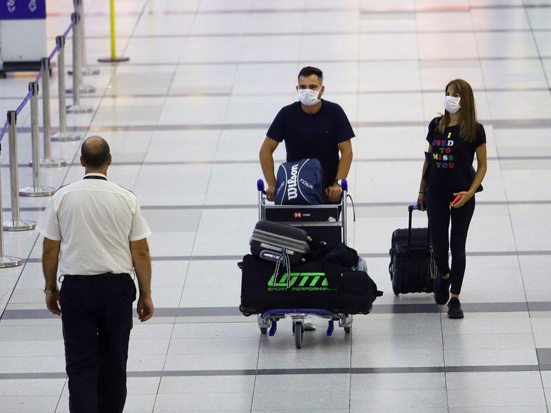 Pasajeros con mascarillas caminan en el Aeropuerto Internacional Ministro Pistarini, en Buenos Aires (Foto: Reuters)