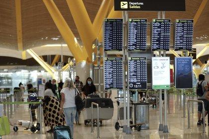 Pasajeros junto a paneles de información en la Terminal T4 del aeropuerto Adolfo Suárez Madrid-Barajas, en Madrid (España) (Jesús Hellín - Europa Press)