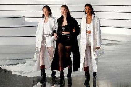 Gigi Hadid junto a dos modelos luciendo la nueva colección de Chanel otoño-invierno 2020/2021 en el Paris Fashion Week. Conjuntos de tweed en blanco y negro de crop top combinadas con medias de nylon con polka dots y botas de caña alta de cuero y las clásicas carteras timeless de la firma