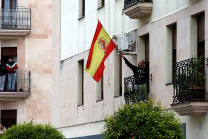 A man waves a Spanish flag from his home in support of healthcare workers, during the coronavirus disease (COVID-19) outbreak, in Ronda, southern Spain, April 4, 2020. REUTERS/Jon Nazca