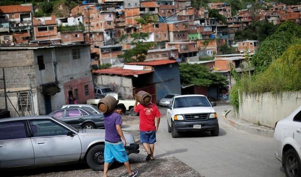 Venezolanos cargan garrafas de gas en Caracas (Reuters)