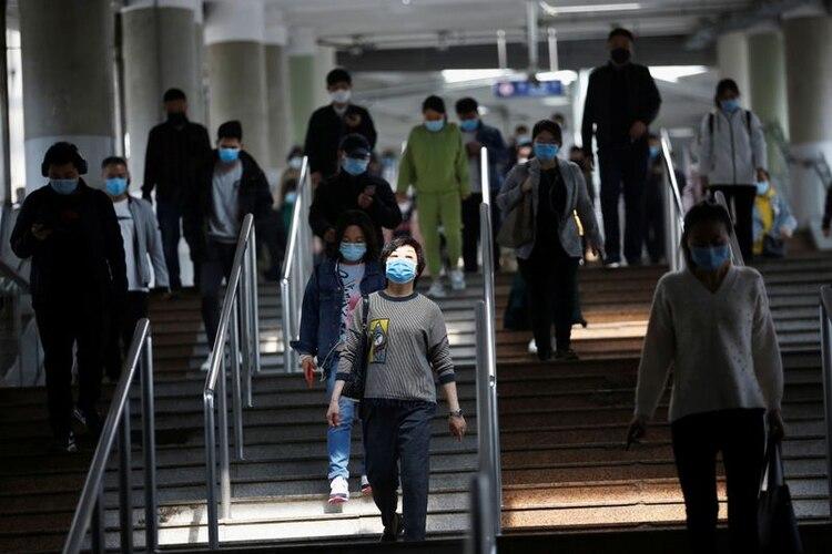 Personas con mascarillas caminan dentro de una estación de metro durante la hora punta de la mañana en Pekín, mientras la propagación de la nueva enfermedad del coronavirus (COVID-19) continúa en el país, China 14 de abril,2020. REUTERS/Tingshu Wang