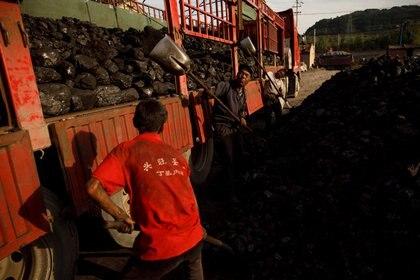 Los trabajadores colocan carbón en un camión en un depósito de carbón cerca de una mina de carbón en Huating, provincia de Gansu, China, el 18 de septiembre de 2020. (REUTERS / Thomas Peter)