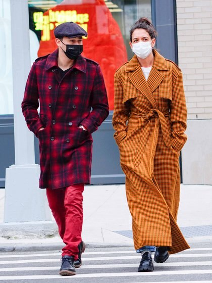 Katie Holmes and her boyfriend, Emilio Vitolo Jr., took a romantic walk through New York and set trends with their looks. The actress wore a jean, patent leather shoes and a long camel plaid coat tied at her waist. The chef, for his part, opted for red pants and a plaid coat of the same color. He completed his outfit with a beret and both wore their respective masks