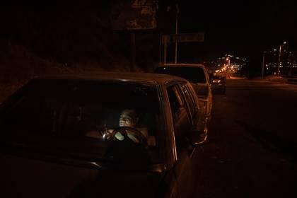 Un hombre que afirmaba haber pasado dos noches en su automóvil veía su teléfono inteligente en una larga fila para comprar gasolina, en Caracas, el 2 de mayo de 2020. (Adriana Loureiro Fernández / The New York Times)