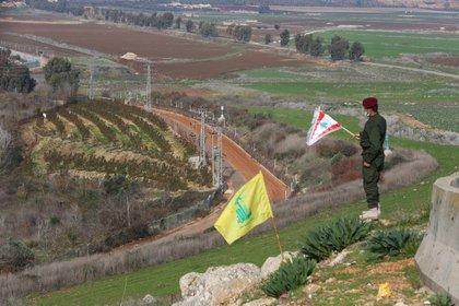 Un miembro de Hezbollah sostiene una bandera libanesa durante una ceremonia en la localidad libanesa del sur de Khiam, cerca de la frontera con Israel, el 3 de enero de 2021 (REUTERS/Aziz Taher)