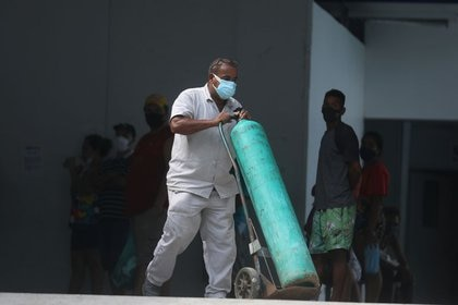 Un trabajador lleva un tanque de oxígeno al interior de un hospital público, durante la pandemia de COVID-19, en la ciudad de Duque de Caxias en el estado de Río de Janeiro, Brasil, 30 de marzo de 2021. REUTERS/Pilar Olivares