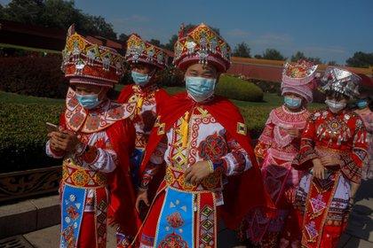 Visitantes de la etnia Miao visten con trajes tradicionales mientras se protegen con mascarillas en Tiananmen en China, Pekín. EFE/ Wu Hong