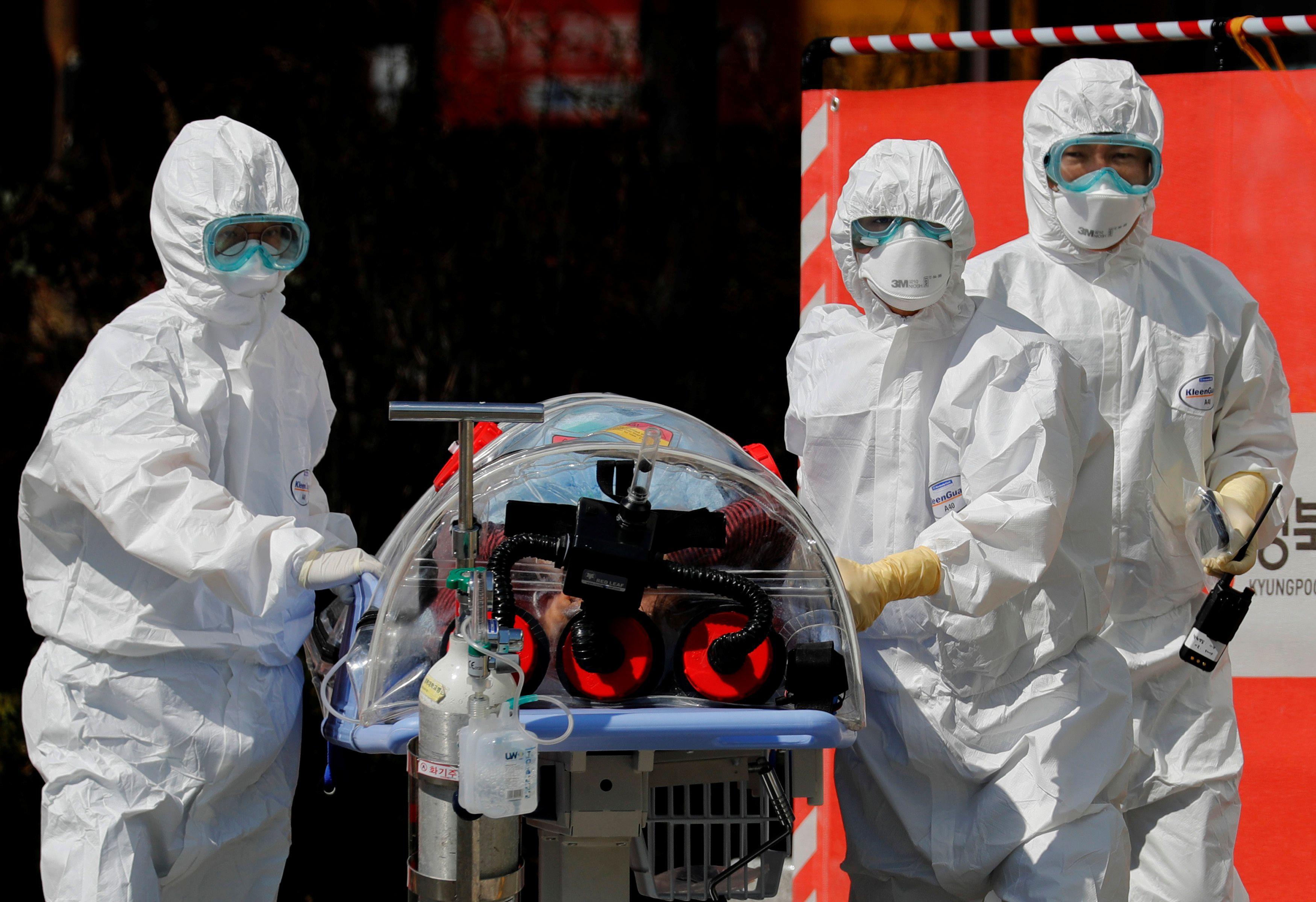 Trabajadores médicos llevan a un paciente en una camilla de aislamiento de presión negativa a una instalación del Hospital Universitario Nacional de Kyungpook en Daegu, Corea del Sur, el 6 de marzo de 2020 (REUTERS/Kim Kyung-Hoon)
