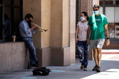 Vista de un hombre tocando trompeta en una calle de Pasadena, California.