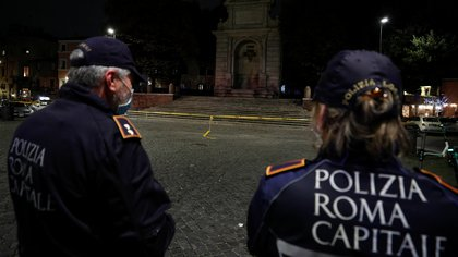 Police officers stand at Piazza Trilussa in Trastevere before it gets closed as areas of Rome prone to large gatherings of people are closed three hours before a midnight curfew to curb the coronavirus disease (COVID-19) infections in Rome, Italy, October 23, 2020. REUTERS/Guglielmo Mangiapane
