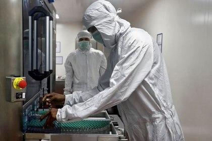 Imagen de archivo de un empleado en equipo de protección personal (PPE) retirando viales de la vacuna COVISHIELD contra el COVID-19 de AstraZeneca desde una máquina de inspección visual dentro de un laboratorio del Instituto Serum de India, en Pune, India. 30 de noviembre, 2020. REUTERS/Francis Mascarenhas/Archivo
