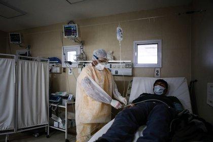 Un enfermero atiende a un paciente en la Unidad de Aislamiento de COVID-19 del Hospital de Agudos en Ezeiza, en la Provincia de Buenos Aires (Foto: EFE)