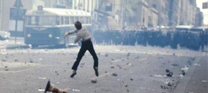 Un joven tirando adoquines durante los enfrentamientos con la policía
