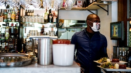 Los empleados de los restaurantes utilizan mascarillas. No así los clientes, que se sientan en largas mesas sin separación.