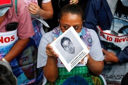 Familiares de estudiantes desaparecidos sostienen carteles con sus imágenes mientras participan en una protesta frente a la Fiscalía General de la República, antes del sexto aniversario de la desaparición de 43 estudiantes de la Escuela Normal Rural de  Ayotzinapa, en la Ciudad de México, México 25 de septiembre de 2020.