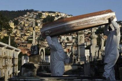Sepultureros llevan el ataúd de Antonia Rodrigues durante su funeral tras fallecer por la enfermedad respiratoria COVID-19 en Río de Janeiro, Brasil [18 de mayo de 2020] (Reuters/ Ricardo Moraes)