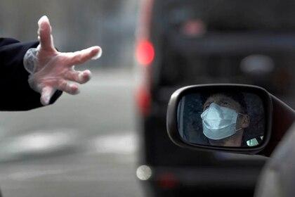 Un oficial de policía habla con un conductor en París, el martes 17 de marzo de 2020