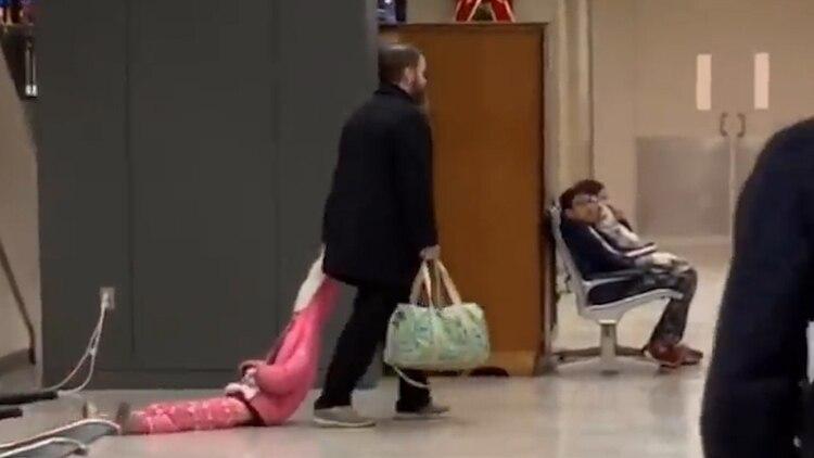 Un hombre arrastra a su hija por el aeropuerto en Virginia (Captura de pantalla)