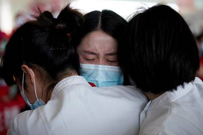 Trabajadores médicos se abrazan en el aeropuerto de Wuhan, en el primer día tras el levantamiento de las restricciones de viajes que pesaron durante meses en la ciudad (Reuters)
