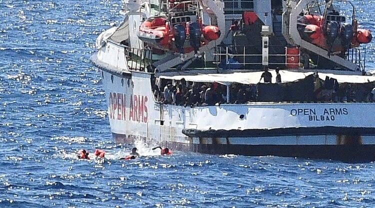 Migrantes nadan tras saltar de la embarcación (Reuters)