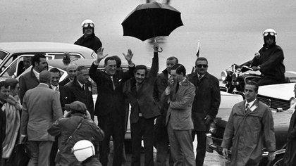 Secuencia de imágenes del regreso, luego de 18 años de exilio, de Domingo Perón a Argentina en el que José Ignacio Rucci sostiene el paraguas para protegerlo de la lluvia. También se distinguen José Lopez Rega e Isabel