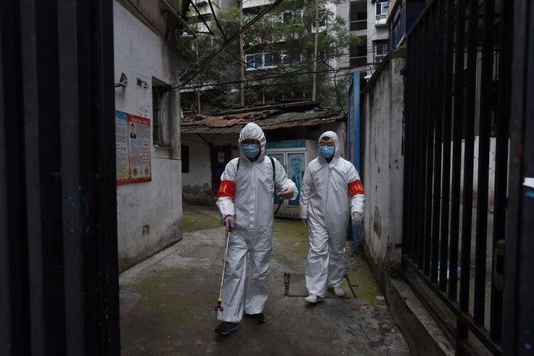 Trabajadores de salud desinfectando un complejo residencial en Wuhan, el epicentro del brote de coronavirus (REUTERS)
