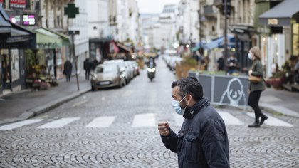 A man wearing a face mask, walks in the Montmartre district of Paris, Sunday Oct.25, 2020. A curfew intended to curb the spiraling spread of the coronavirus, has been imposed in many regions of France including Paris and its suburbs. (AP Photo/Lewis Joly)