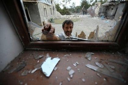 Un hombre quita vidrios rotos de una ventana en Garagoyunlu, Azerbaiyán (REUTERS/Aziz Karimov)