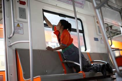 Un trabajador limpia las ventanas de un vagón de metro.