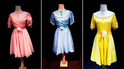 """Tres vestidos """"de niña"""" en fucsia, celeste y amarillo. Son iguales, en telas brillosas, de excelente calidad y caída, con broderíes y detalles como moños en cintura adelante y atrás. El precio base de cada uno es de $ 12.000, y el combo de los 3 juntos, de $ 30.000"""