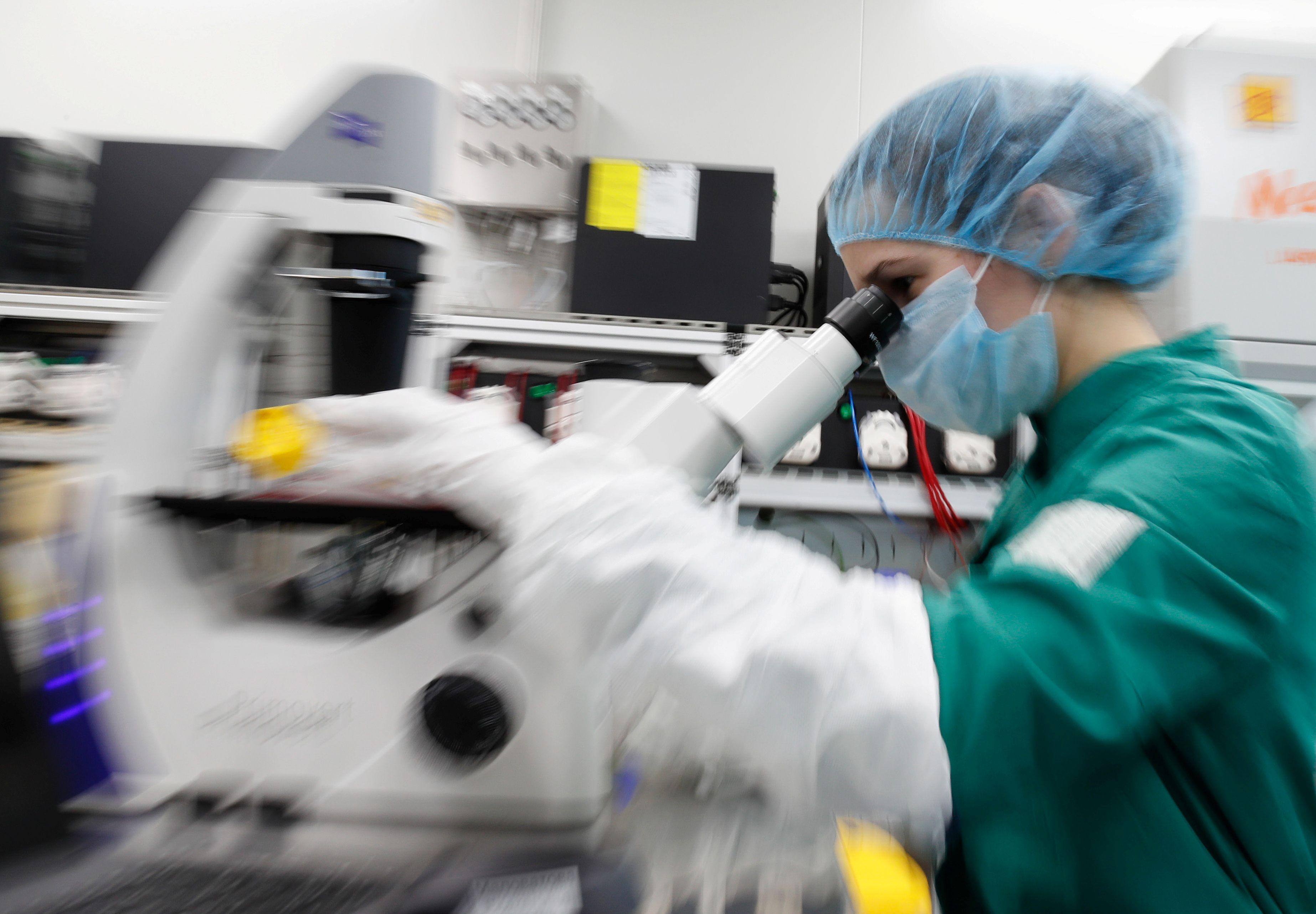 Una investigadora en San Petesburgo analiza el coronavirus bajo un microscopio potente - REUTERS/Anton Vaganov
