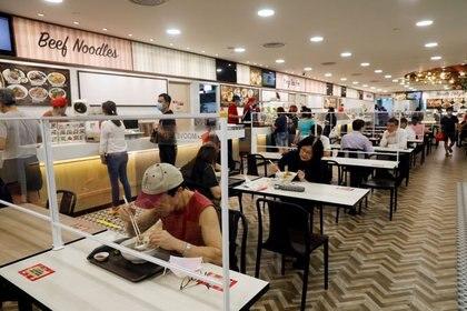 La gente come en una mesa instalada con divisores de plexiglás en un patio de comidas en Singapur mientras la ciudad-estado impone el distanciamiento social para combatir la propagación de la enfermedad del coronavirus (COVID-19), 19 de junio de 2020. (REUTERS / Edgar Su / archivo)
