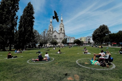 Residents enjoy the warm weather while maintaining safe gatherings inside new social distancing circles as a pigeon takes flight at Washington Square in front of Saints Peter and Paul Church in the North Beach neighborhood in San Francisco, California, USA, 22 May 2020. EFE/EPA/JOHN G. MABANGLO