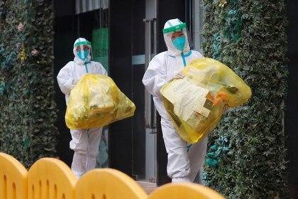 Dos trabajadores de la Organización Mundial de la Salud (OMS) con equipos de protección individual (EPI) encargados de investigar el origen del nuevo coronavirus (SARS-CoV-2) en Wuhan, provincia de Hubei, China el 28 de enero de 2020. REUTERS/Thomas Peter