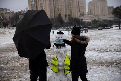 La gente juega con nieve en un parque en una mañana nevada en Jerusalén, 18 de febrero de 2021. REUTERS / Ronen Zvulun