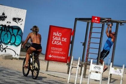 """Una mujer que monta una bicicleta pasa un cartel que dice """"No salgas de la casa"""" en la playa de Ipanema, durante el brote de la enfermedad por coronavirus (COVID-19), en Río de Janeiro, Brasil, 5 de abril de 2020. (REUTERS / Pilar Olivares)"""