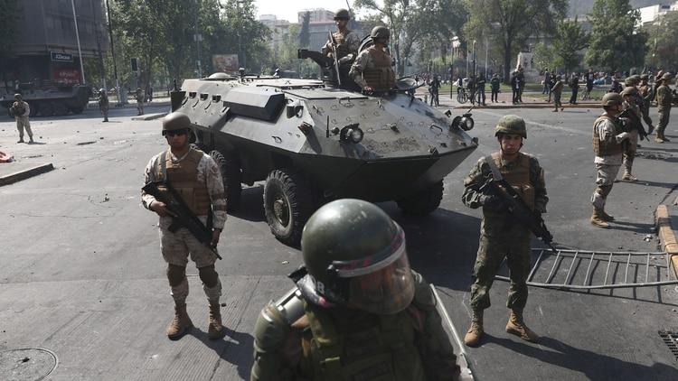 Soldados vigilan a manifestantes en Santiago de Chile (Reuters)