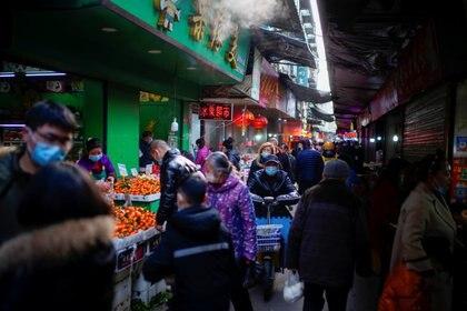 Personas con mascarillas caminan en un mercado callejero en Wuhan, provincia de Hubei, China, el 8 de febrero de 2021. REUTERS / Aly Song
