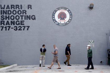 Un grupo de clientes mantiene el distanciamiento social mientras esperan para entrar a una tienda de armas de fuego, en Doral, Florida (AP Foto/Lynne Sladky)