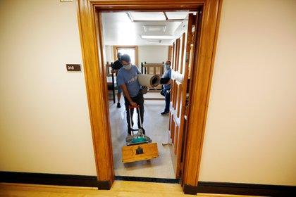 Un alumno de la universidad de Carolina del Norte lleva sus pertenencias luego de que la universidad determinara que los estudiantes debían mudarse fuera del campus ante el aumentod e casos de Covid-19. Foto: REUTERS/Jonathan Drake
