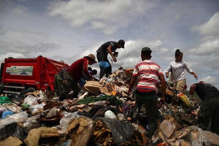Migrantes venezolanos en un vertedero de basura en la ciudad fronteriza de Pacaraima, Brasil, el 15 de abril de 2019. (REUTERS)
