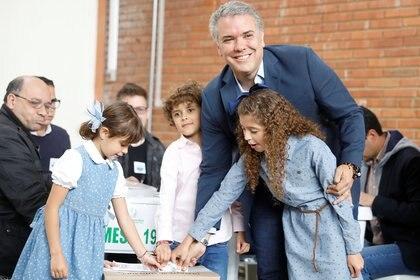 Acompañado de sus tres hijos, el candidato uribista Iván Duque depositó su voto.(Reuters)