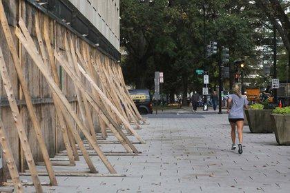 Una mujer trota delante de tablas de madera levantadas para proteger comercios en Estados Unidos durante las elecciones. Foto: REUTERS/Leah Millis