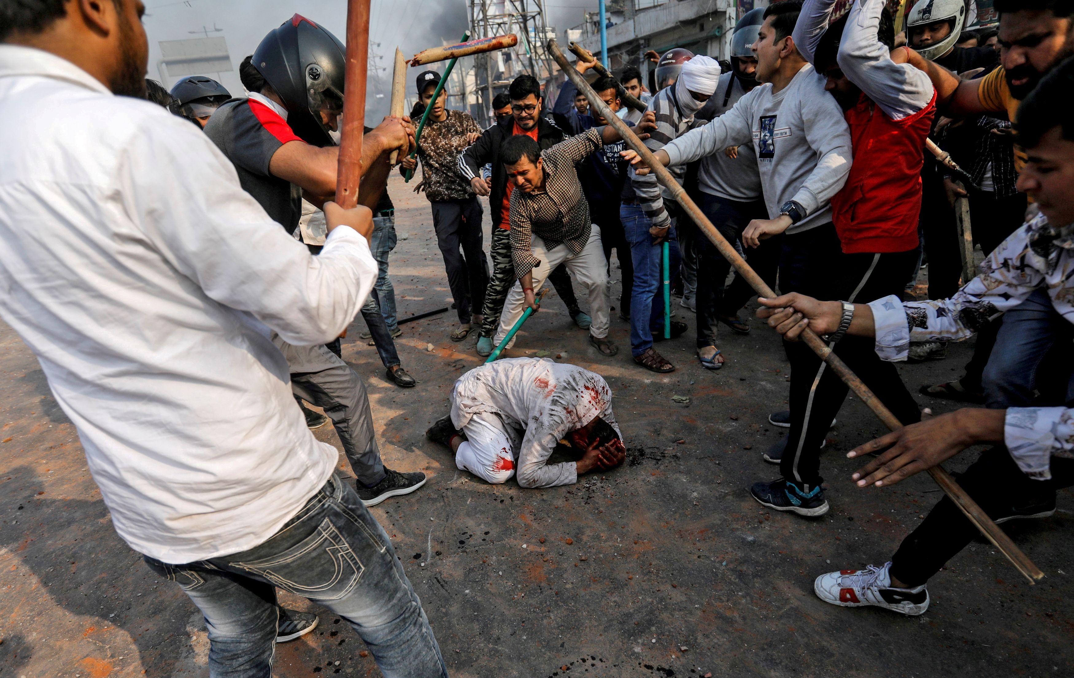 Un grupo de hombres que corean lemas pro-hindúes, golpean a Mohammad Zubair, de 37 años, que es musulmán, durante las protestas provocadas por una nueva ley de ciudadanía en Nueva Delhi, India, 24 de febrero de 2020.