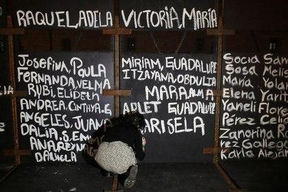 Una mujer pinta los nombres de víctimas de feminicidio en México en las vallas colocadas frente al Palacio Nacional antes de una protesta por el Día de la Mujer (Foto: REUTERS/Henry Romero)