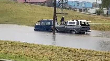 Una camioneta empuja a otro vehículo para sacarlo del agua