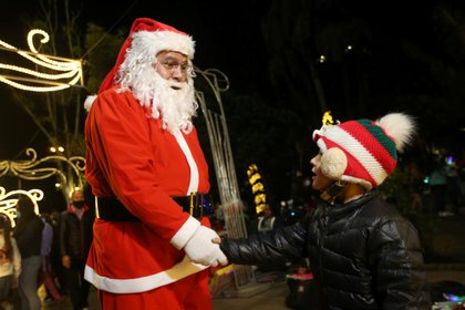 Un niño con una máscara debajo de su barbilla saluda a un hombre vestido de Papá Noel en Bogotá (REUTERS/Luisa González)